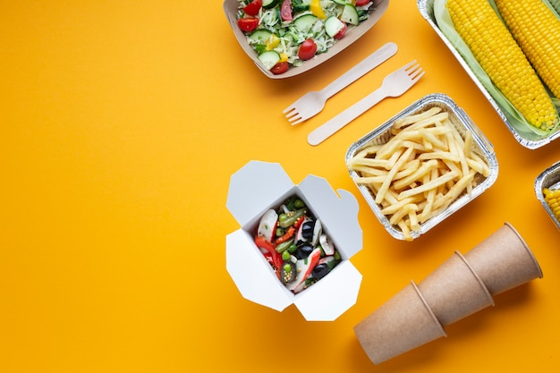 Flat lay arrangement with fries, salad and corn