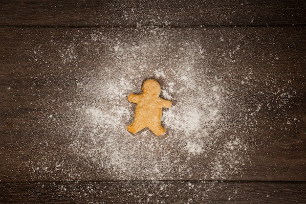 Flat lay arrangement with gingerbread man cookie and flour