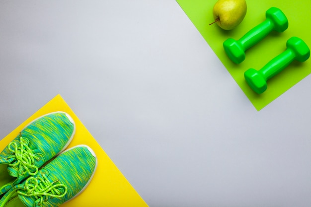 Flat lay arrangement with green shoes and dumbbells