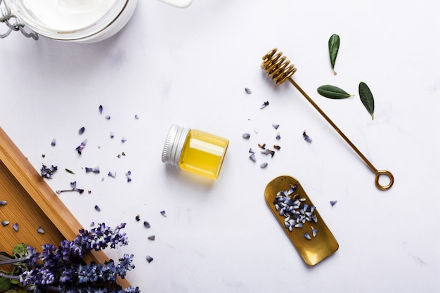Flat lay arrangement with honey bottle and flower