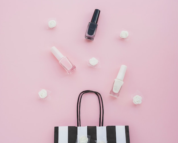 Flat lay arrangement with nail polish and bag