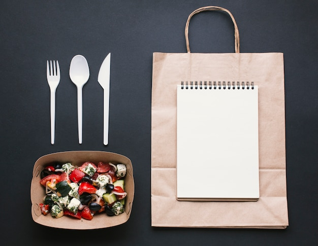 Flat lay arrangement with notebook on paper bag