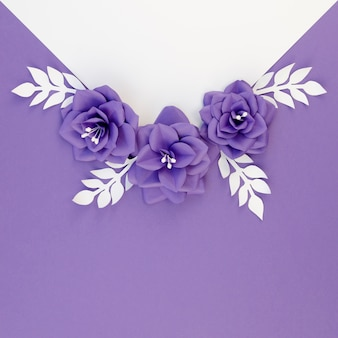 Flat lay arrangement with paper flowers and purple background