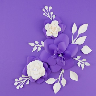 Flat lay arrangement with paper flowers on purple background