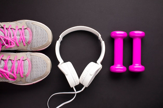 Flat lay arrangement with pink dumbbells and headphones