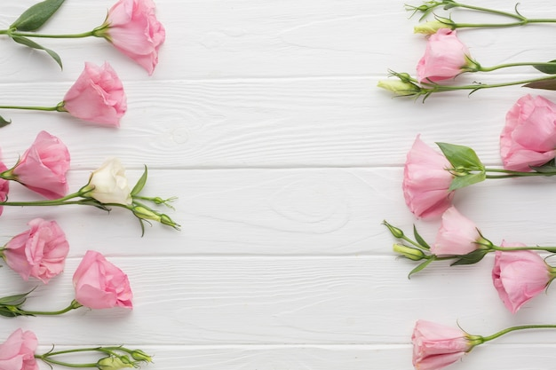 Flat lay arrangement with pink roses on wooden background