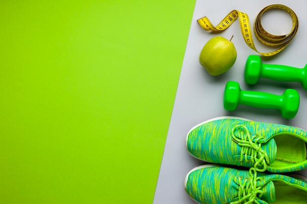 Flat lay arrangement with running shoes and dumbbells