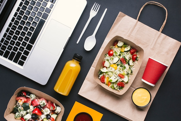 Flat lay arrangement with salad and laptop