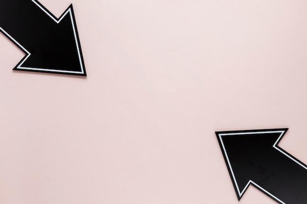 Frecce piane di disposizione su backgroound rosa con lo spazio della copia