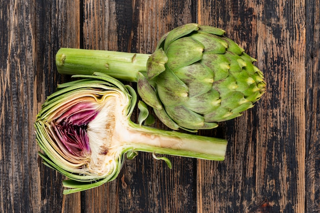 Flat lay artichoke and a slice on dark wooden background. horizontal