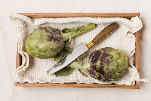 Flat lay of artichokes and knife