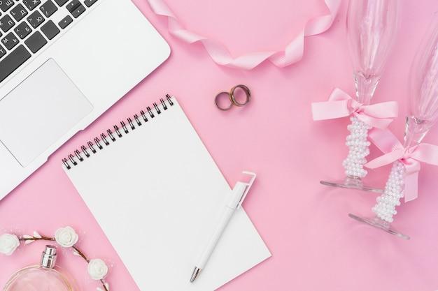 Flat lay artistic wedding arrangement on pink background