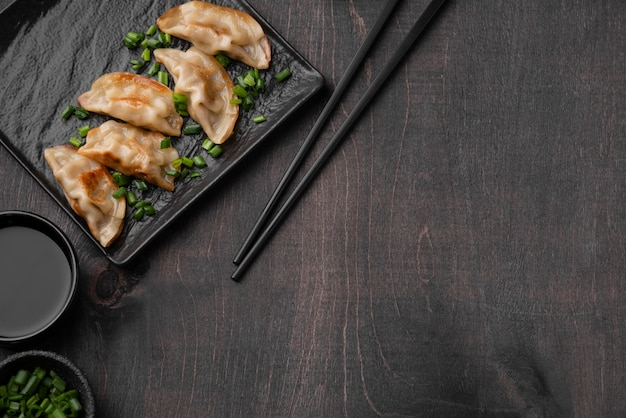 Flat lay of asian dumplings dish on slate with copy space