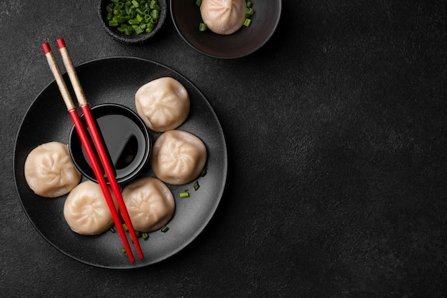 Flat lay of asian dumplings with chopsticks and copy space