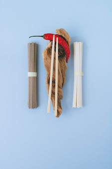 Flat lay asian noodles, red chili, chopsticks on wooden sticks on a bright blue background