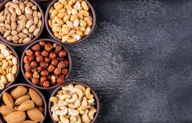 Flat lay assorted nuts and dried fruits in mini different bowls with pecan, pistachios, almond, peanut