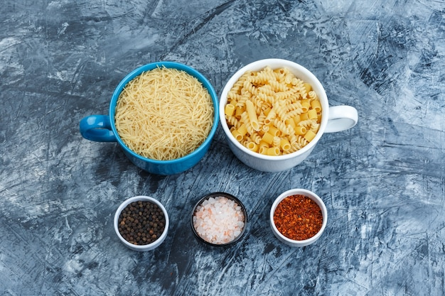 Flat lay assorted pasta in bowls with spices on grey plaster background. horizontal
