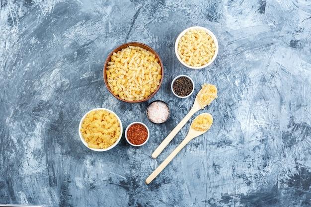 Piatto assortito laici pasta in ciotole e cucchiai di legno con spezie su una schifezza sullo sfondo di gesso. orizzontale
