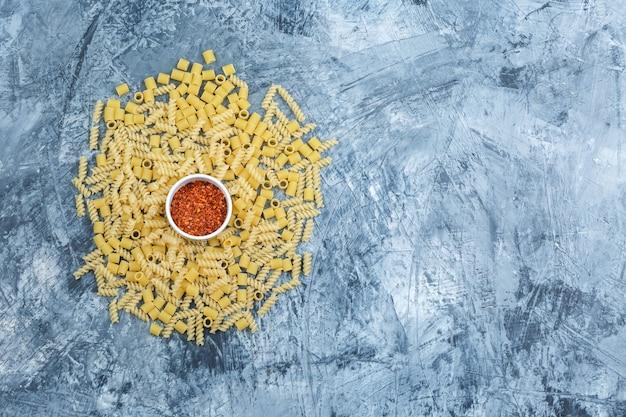Piatto assortito laici pasta con fiocchi di pepe rosso su una schifezza sullo sfondo di gesso. orizzontale