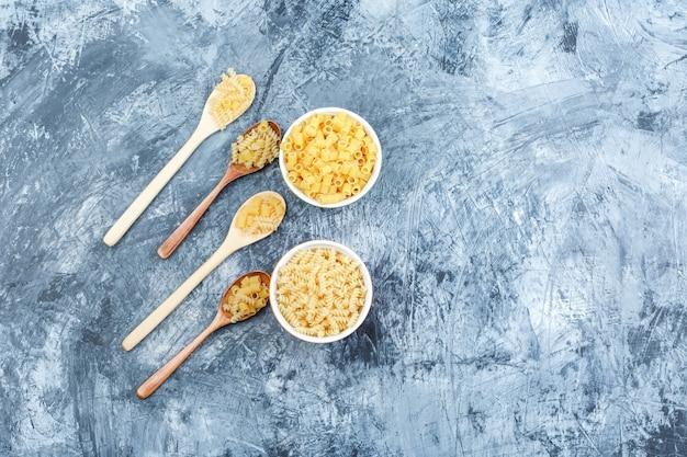 Piatto assortito laici pasta in cucchiai di legno e ciotole su una schifezza sullo sfondo di gesso. orizzontale