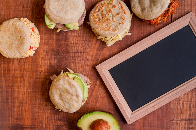 Flat lay of assortment of arepas with chalkboard