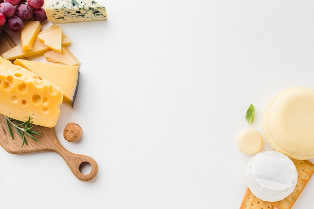 Flat lay assortment of cheese on wooden cutting board