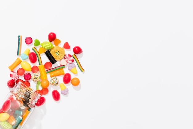 Flat lay assortment of colorful candies on white background with copy space