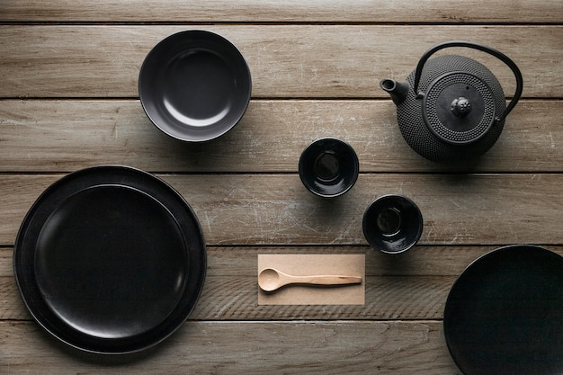 Flat lay of assortment of dinnerware with teapot and wooden spoon