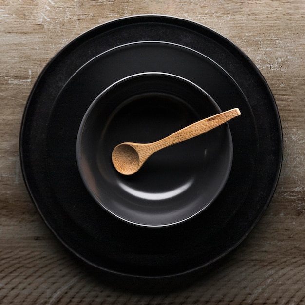 Flat lay of assortment of dinnerware with wooden spoon
