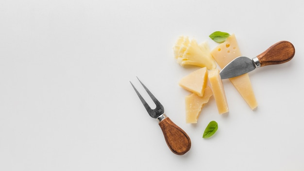 Flat lay assortment of gourmet cheese and cheese knives with copy space