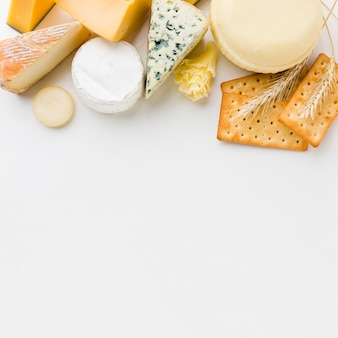 Flat lay assortment of gourmet cheese and crackers with copy space