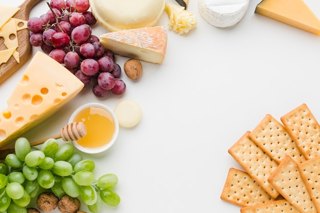 Flat lay assortment of gourmet cheese and grapes with crackers