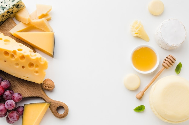 Flat lay assortment of gourmet cheese and honey with copy space