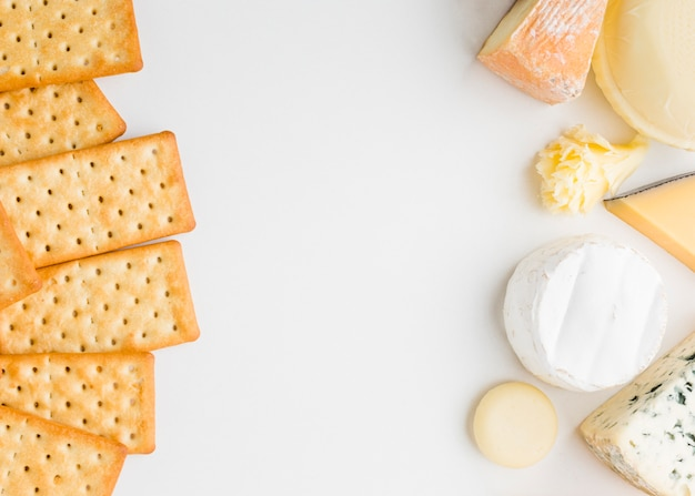 Flat lay assortment of gourmet cheese with crackers