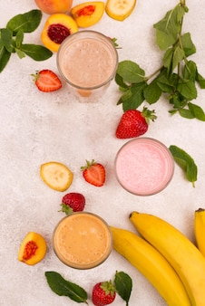 Flat lay of assortment of milkshakes with peach and banana