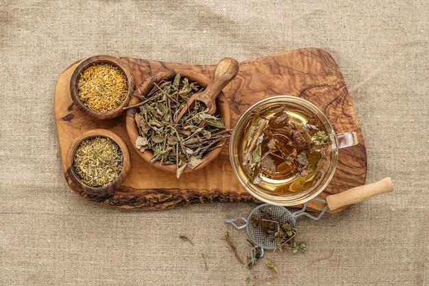 お茶のカップに乾燥した植物のフラットレイの品揃え