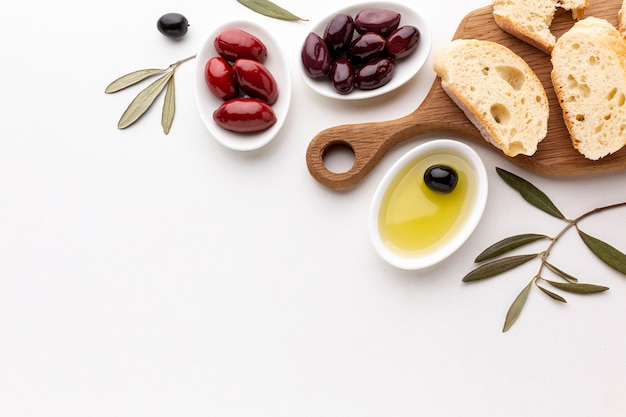Flat lay assortment of olives bread slices and olive oil with copy space
