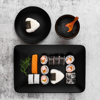 Flat lay assortment of sushi on black rectangular plate with copy space