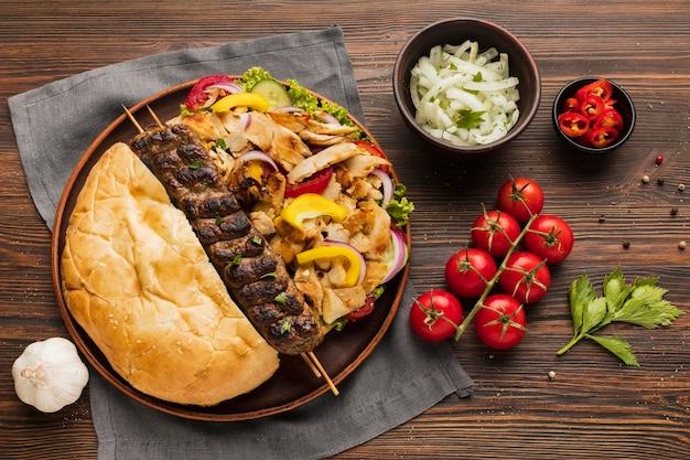 Lay piatto di assortimento di gustosi kebab con pomodori ed erbe aromatiche