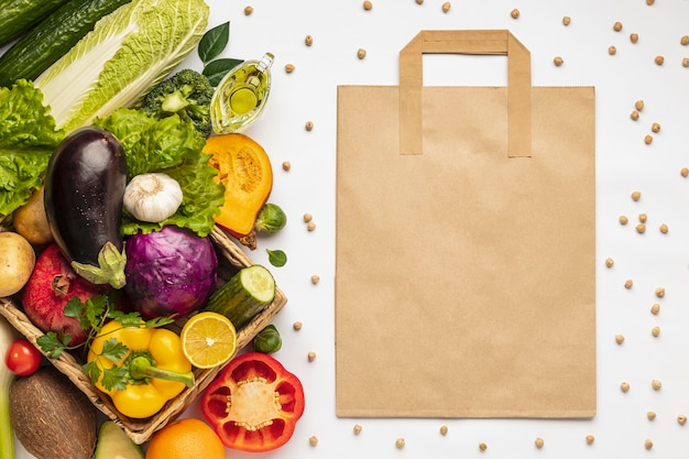 Flat lay of assortment of vegetables with grocery bag