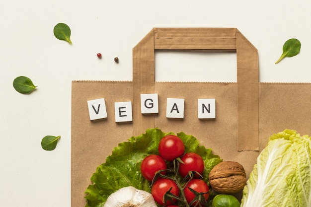 Flat lay of assortment of vegetables with paper bag and the word vegan