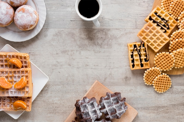 Flat lay of assortment of waffles with coffee and doughnuts