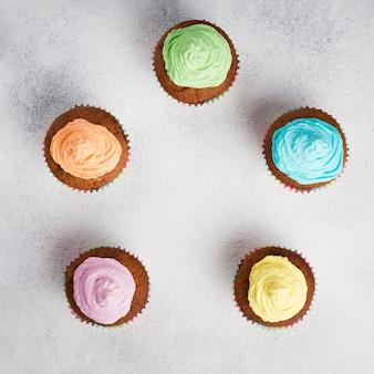 Плоский ассортимент с вкусными кексами и белым фоном