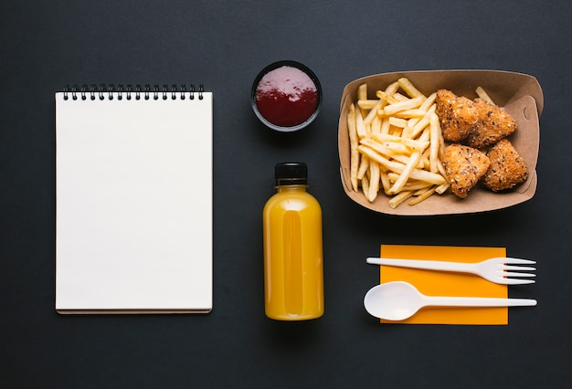 Flat lay assortment with fries and notebook