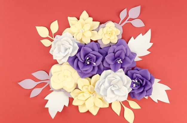 Flat lay assortment with paper flowers and red background