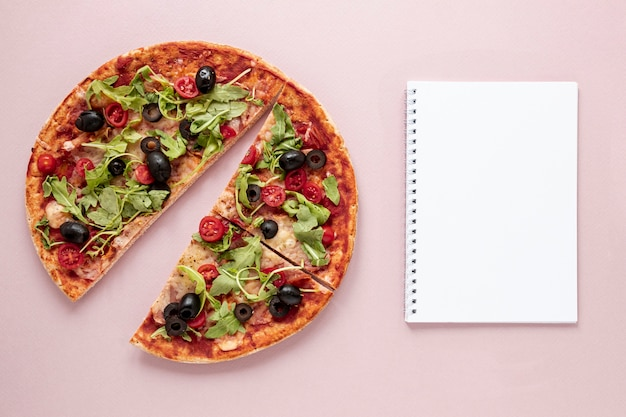 Flat lay assortment with pizza and notebook