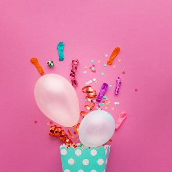 Flat lay assortment with with white balloons and confetti