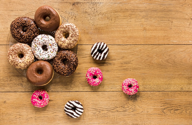 Flat lay of assortments on donuts on wooden surface