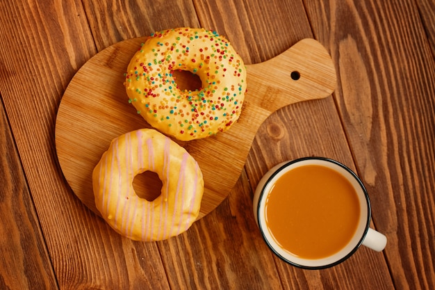 Flat lay of the autumn composition a mug of carrot juice and two sweet doughnuts with yellow glaze p...