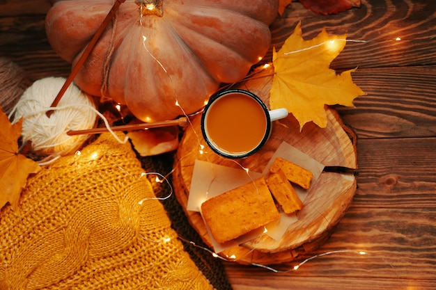 Flat lay of autumn composition for postcards hot coffee and pumpkin pie on a wooden tray ripe pumpki...